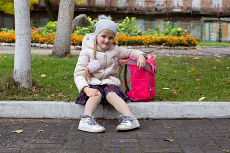 Joyful pupil with a backpack sitting on the curb 写真素材