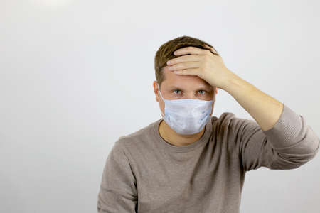A man with a headache in a medical mask looks at the camera and holds his forehead with his hand.