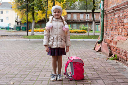 Schoolboy girl stands on the street with a backpack. The child is waiting to be picked up after school 写真素材 - 158814213