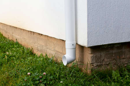 White plastic downpipe at the corner of a new home 写真素材 - 158815141