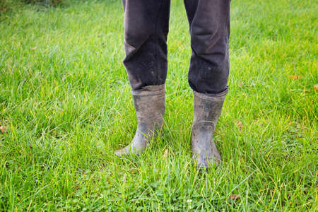 Dirty rubber boots on bright green grass