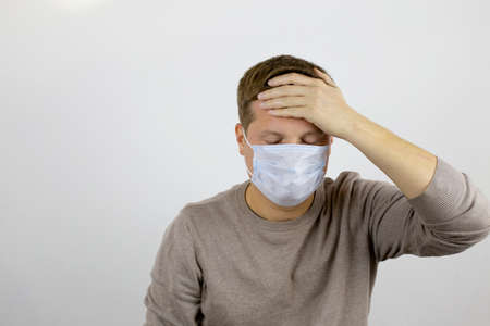 A man in a medical mask suffers from malaise and holds on to his forehead with one hand. 写真素材