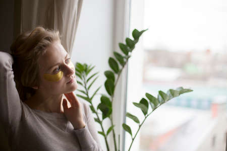 The beautiful woman by the window applied gold anti-wrinkle patches 写真素材 - 162984737