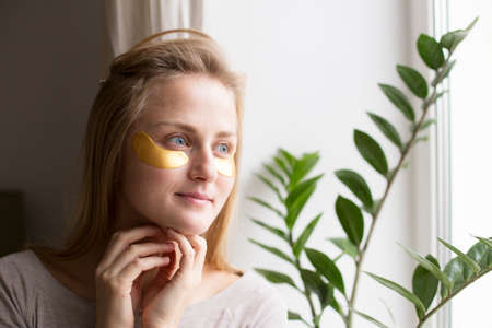 Beautiful woman near the window with patches under the eyes. The concept of skin care 写真素材
