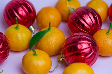 Orange tangerines and red balls lie against a pink background. Delicious background. 写真素材 - 163300590