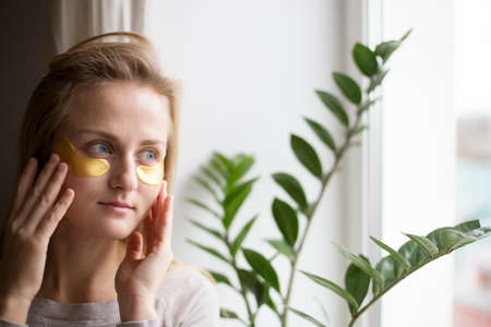 Woman near the window with patches under the eyes. The concept of the skin around the eyes 写真素材 - 163301540