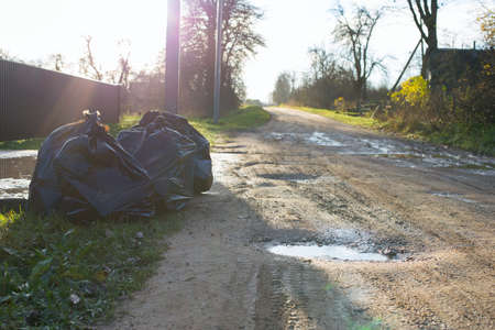 Large black plastic garbage bags are on the road outside the houses. Garbage collection in the private sector