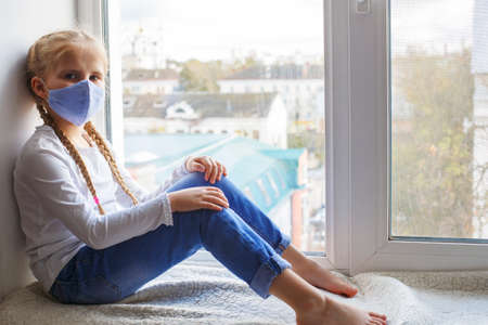 A child in a mask sits on the windowsill and is sad that he is alone and sick