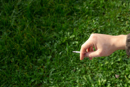Cigarette in a mans hand on a background of summer grass.