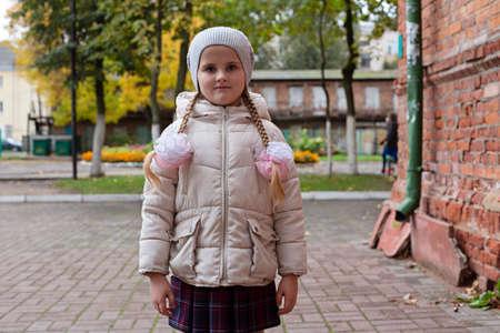 Girl schoolgirl in school uniform standing in the street. 写真素材