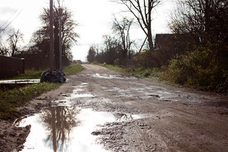 The road with puddles. Garbage bags standing on the road with puddles. 写真素材 - 165555022