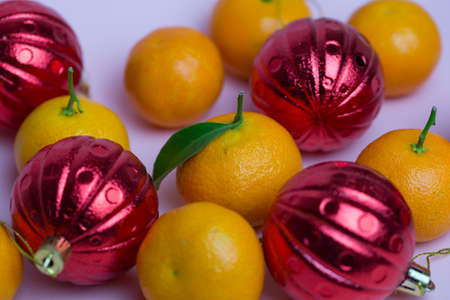 Orange tangerines and red balls lie against a pink background