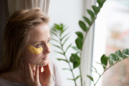Woman doing daily skin care at home. Golden patches under the eyes to moisturize the skin. 写真素材