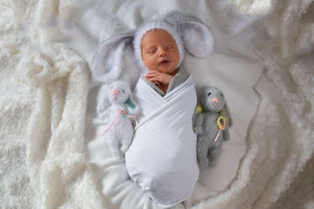 Newborn baby boy with soft toys hares. Newborn in a hat with ears