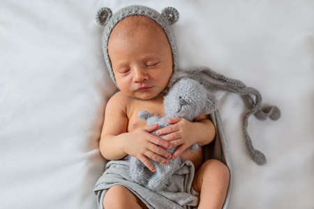 Portrait of a newborn sleeping baby with a toy in a hat with ears 写真素材