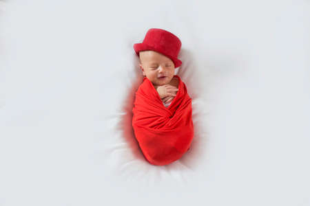 New born baby in a red suit and hat on a white background. Sleeping newborn boy in a red top hat with a smile on his face.