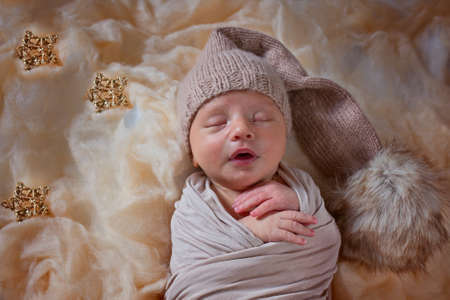 New born sleeping child in a hat with pompom lies against the starry sky.