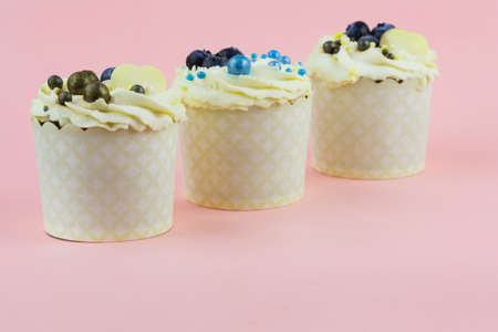 Festive cupcakes with berries and decor on a pink background 写真素材