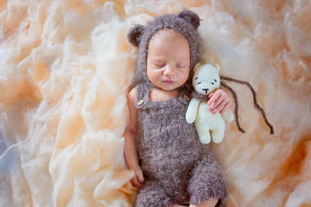 A very gentle and beautiful photo of a newborn boy in a hat with ears and a toy in his hands. Sleeping newborn baby with toy 写真素材
