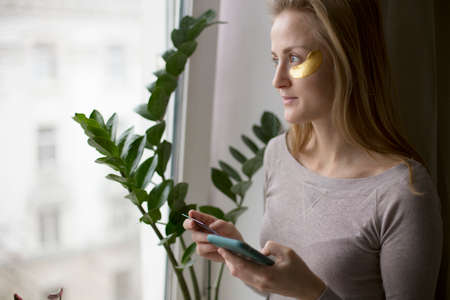 A European woman makes online purchases standing by the window and taking care of her skin.