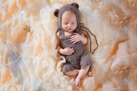 New born sleeping baby in a bear costume. Beautiful posing of a newborn baby in a hat with ears and overalls. Professional photo of a newborn baby