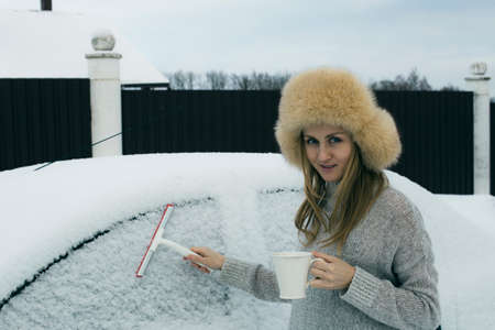 A young girl with a mug and a scraper cleans the car from snow. The girl cleans the car of snow 写真素材