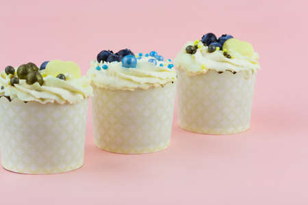 Three cupcakes on a pink background. Wedding confectionery Stock Photo