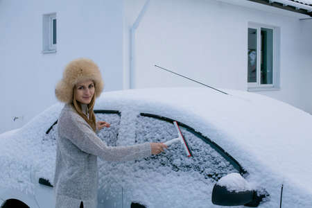 A young girl smiles at the camera and cleans the car from snow. Winter in Europe Stock Photo