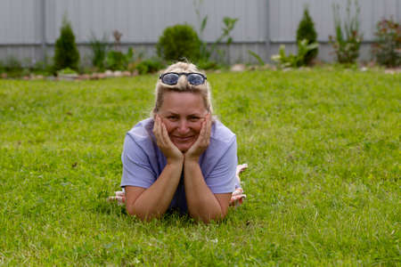 Caucasian woman lies on the grass and enjoys life Stock Photo