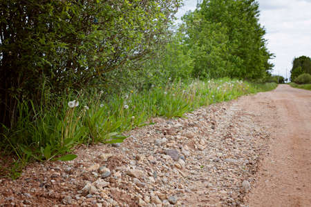Road side.The road is made of gravel and clay. Summer road outside the city. Stock Photo