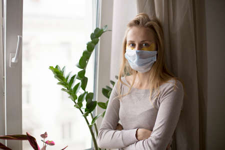 A woman is standing by the window wearing a medical mask. Anxiety about health, illness, emotional exhaustion