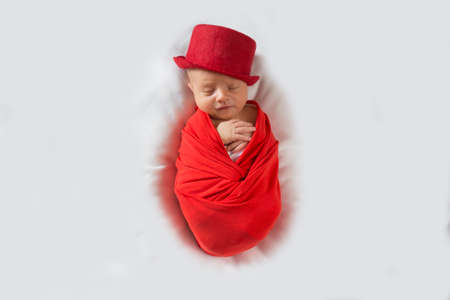 Newborn sleeping baby sleeping sweetly in a red top hat. Cute newborn baby in a red suit and hat.