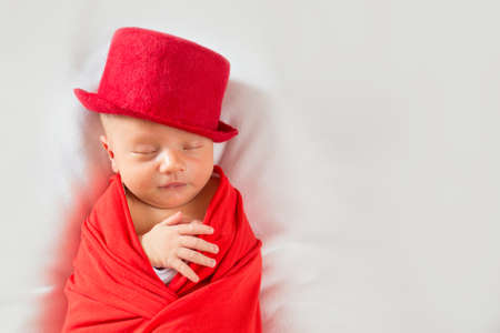 Portrait of newborn gentleman in the cylinder. Sleeping newborn baby in a red suit and hat Stock Photo