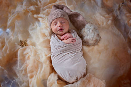 Newborn sleeping baby. Little sleeping boy in a suit with a pompom and an asterisk Stock Photo