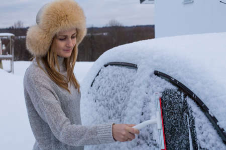 The woman is forced to clear snow from her car