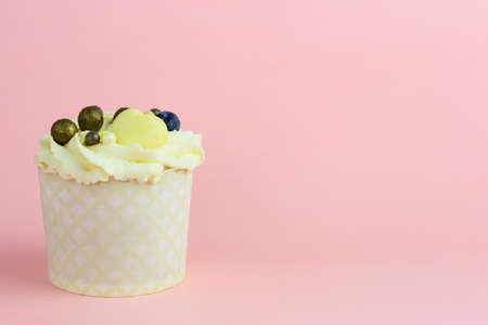 Beautiful lemon cupcake with a decoration from berries on a pink background