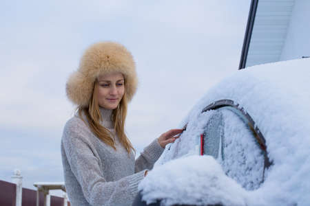 A young girl drinks coffee and clean the car from snow Stock Photo