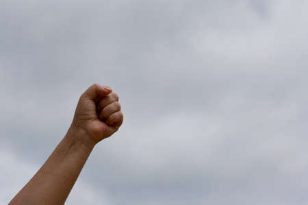 Clenched fist up against the sky. Struggle and leadership concept