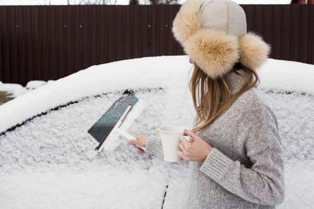 Photo of a girl who cleans the glass of a car from snow.