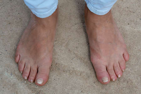 Bare feet of a woman aged on the concrete floor. Female feet without shoes Stock Photo