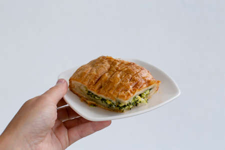 A small slice of spinach . Healthy breakfast. Hand holding a plate of pie