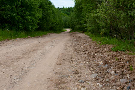The road is made of gravel and clay. Summer road outside the city. Long road between trees