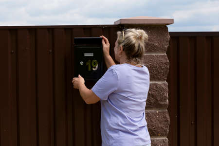 A woman checks a mailbox outside her house. A woman goes to a mailbox and checks it.