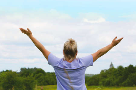 A woman with her arms outstretched up to the sky stands in front of the field. The concept of freedom and good mood. Love for everything in this world Stock Photo