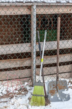 Tools and equipment - a broom, a shovel and an ice pick for cleaning cages of a shelter for homeless dogs. In the background, dogs in cages. Around the snow-covered land. Zdjęcie Seryjne