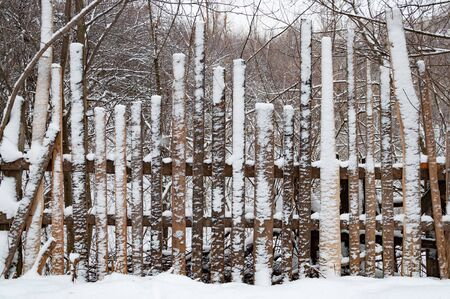 An old wooden fence made of boards of different heights covered with snow. Behind the fence is a deep snow covered ravine overgrown with forest Reklamní fotografie