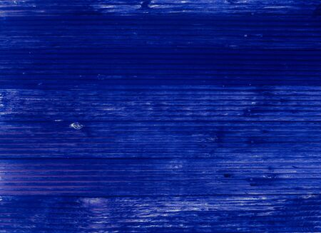 Texture of an old wooden wall. Abstract background tinted in deep blue. Color of the year 2020 Classic Blue