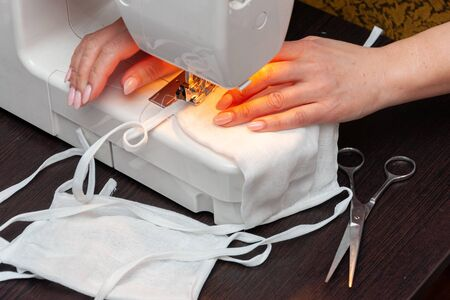 A woman with a beautiful pink manicure sews a homemade protective face mask from fabric. Close-up of a sewing machine and a woman's hands.