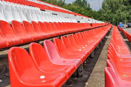 Empty seats in the stands of the arena or auditorium. Rows of red and white stadium seats without spectators. The concept of the abolition of sports and mass entertainment events