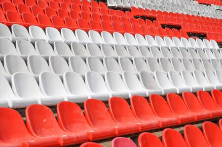 Empty seats in the stands of the arena or auditorium. Rows of red and white stadium seats without spectators. Concept of cancellation of mass sports and entertainment events